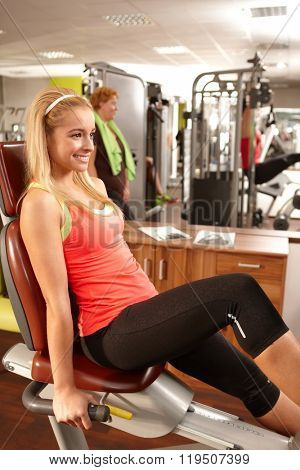 Pretty young blonde girl training in gym.