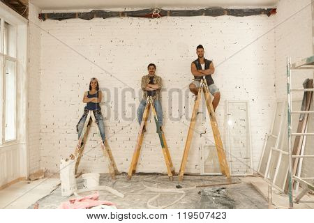 Team photo of workers renovating house, sitting on top of ladder, smiling arms crossed.