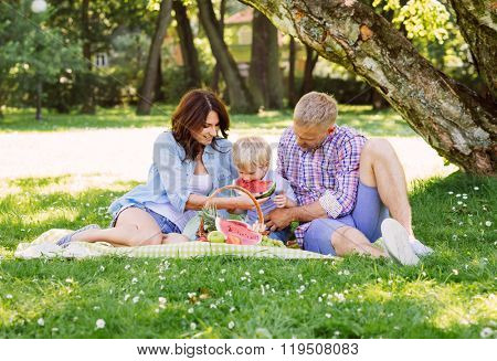 Happy family having a picnic in the park eating a watermelon.