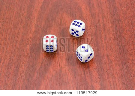 Three Traditional Six-sided Dice On Wooden Surface
