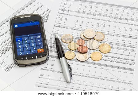 Coins, Pen, Smartphone In Calculator Mode On The Data Table