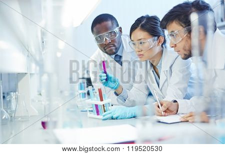 Group of young scientists studying new substances in flasks