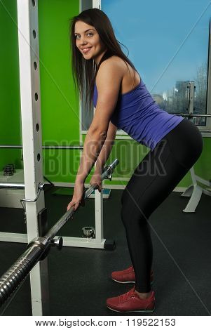Attractive woman doing exercise with weight bar