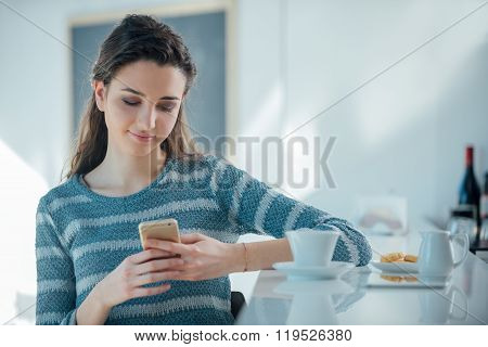 Girl With Mobile Phone Sitting At The Bar Counter