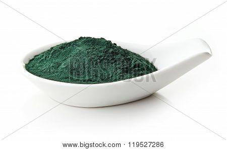 Spirulina Powder In White Porcelain Spoon On White Background