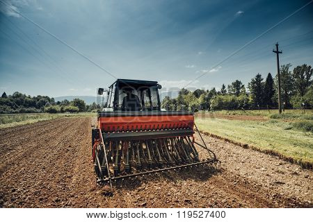Farmer In The Fields Driving A Tractor