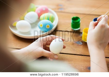 easter, holidays, tradition and people concept - close up of woman coloring easter eggs with colors and brush
