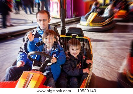 Father And His Two Sons Having A Ride In The Bumper Car At The Fun Fair