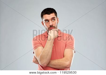 doubt, expression and people concept - man thinking over gray background