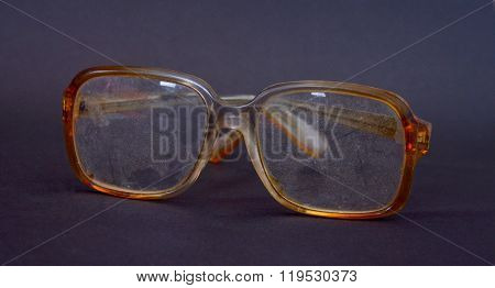 Old and dusty eyeglasses on dark background