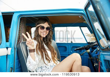 summer holidays, road trip, vacation, travel and people concept - smiling young hippie woman showing peace gesture in minivan car