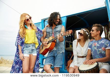 summer holidays, road trip, vacation, travel and people concept - happy young hippie friends having fun and playing music over minivan car