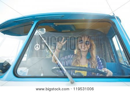 summer holidays, road trip, vacation, travel and people concept - smiling young hippie woman driving minivan car and showing peace gesture