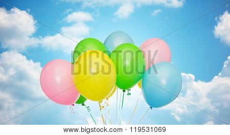 holidays, birthday, party and decoration concept - bunch of inflated colorful helium balloons over blue sky and clouds background