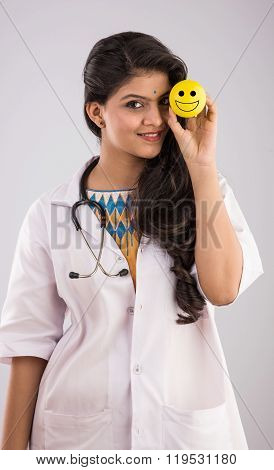 Young indian lady doctor holding a yellow smiley face emoticon in her hand, happyness and well being