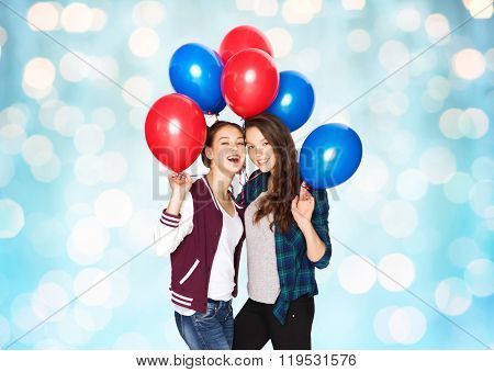 people, friends, teens, holidays and party concept - happy smiling pretty teenage girls with helium balloons over blue lights background