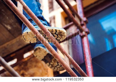 Detail of legs of unrecognizable man standing on scaffold