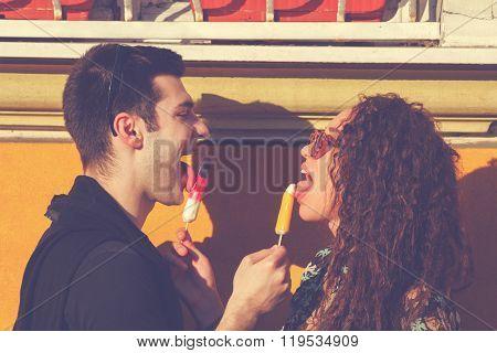 Urban couple outdoors eating ice-cream on the street.