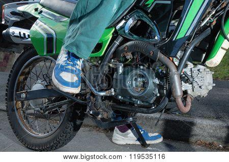 Teenage Boy Kick Starting A Motorbike