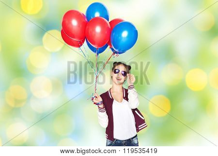 people, teens, holidays, party and summer concept - happy smiling pretty teenage girl in sunglasses with helium balloons over green lights background