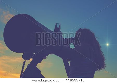 Silhouette of  a girl stargazing through a telescope.