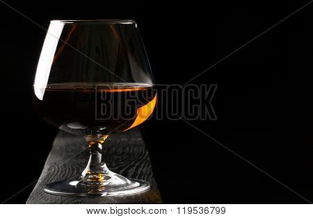Glass Of Cognac On The Black Table