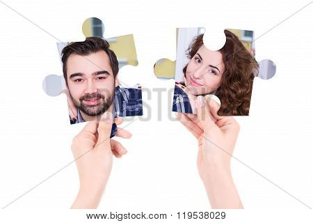 Love Concept - Two Puzzle Pieces With Man And Woman Portraits In Female Hands Isolated On White
