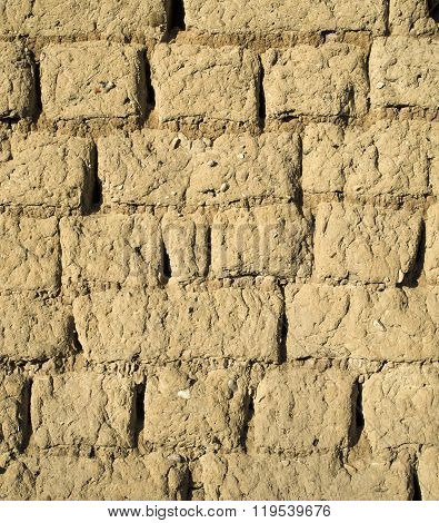 Wall of old adobe house closeup in sunny day