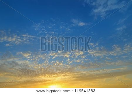 Background photo of natural Clouds formation on a blue sky in the evening with yellow shade of the sun