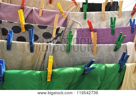 Colored Clothespins Hold The Clothes On A Rope