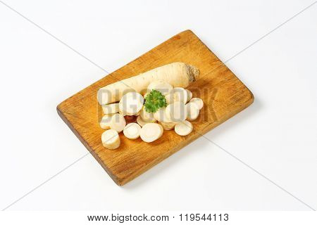 sliced root parsley on wooden cutting board