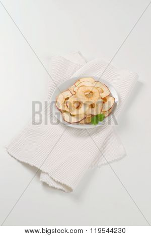 plate of dried apple chips on white place mat