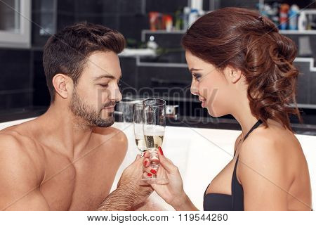 Happy Couple With Glasses Of Champagne In Jacuzzi