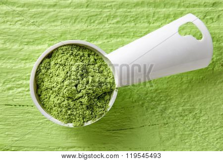 Measuring Scoop Of Barley Or Wheat Grass Powder On Green Background
