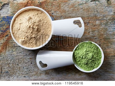 Measuring Scoops Of Maca And Barley Or Wheat Grass Powders