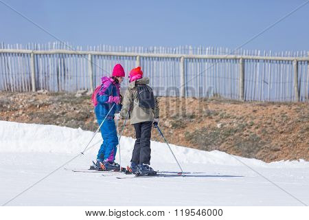 Two Female Skiers Talking