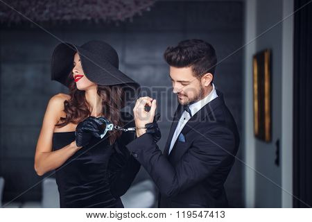 Sexy Woman In Hat Holding Young Rich Lover On Handcuffs Indoor