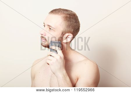 bearded guy shave electric razor