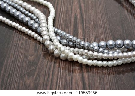 Strings of pearl beads on dark background