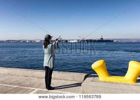 Woman Taking Photos Of The Bay Of San Diego While Walking On Pier During Nice Day