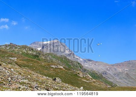 Transport Helicopter Flying With Supplies And Mountain Panorama With Alpine Hut In Hohe Tauern Alps,