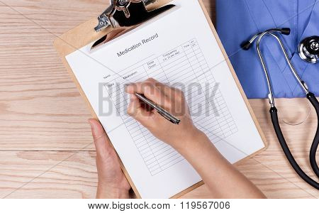 Doctor Working On Patient Medication Form With Medical Objects On Wooden Desktop