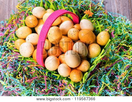 Easter Eggs In Basket On Top Of Colorful Mache Paper With Rustic Wooden Boards