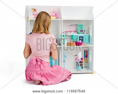 Little Girl Is Playing With The Dollhouse Full Of Dolls And Furniture