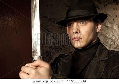 A dangerous man holding dagger on dark background