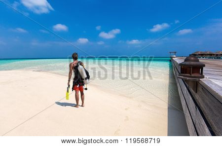 Mal scuba diver walking on the beach