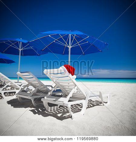 Santa Helper Hat On Sun Bed At Caribbean Beach With Blue Sun Umbrellas