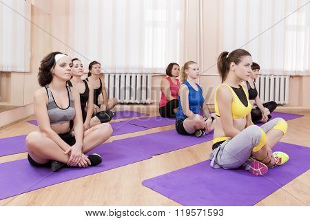 Sport, Fitness And Pilates Concepts. Group Of Seven Caucasian Female Athletes Stretching Leg Muscles