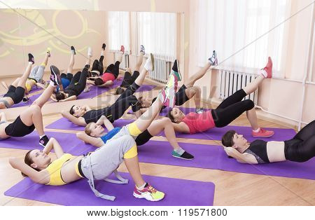 Fitness Concept And Ideas. Group Of Seven Female Athletes Performing Legs Stretching Exercise on Mat