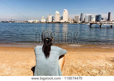 Woman Enjoying The View Of The San Diego Bay And Skyline While Sitting At Beach